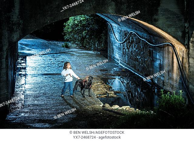 Lonely girl with her pet dog in a tunnel at night time