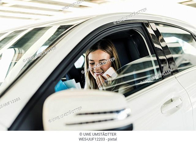 Smiling young woman with cell phone in car