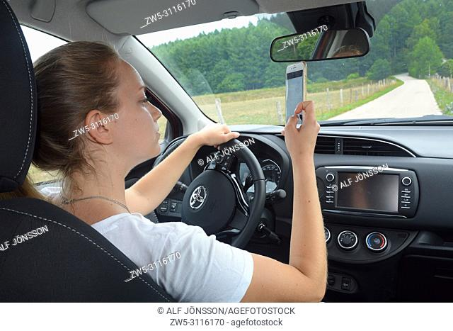 Young woman, 25 years old, uses a mobil phone while she drive a car on a country road in Scania, Sweden, Europe