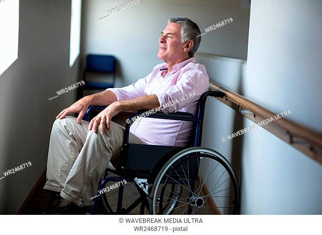 Senior man sitting on wheelchair and looking through window at home