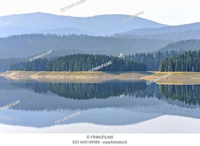 Daylight misty view to Oasa dam lake with mountains full of green trees and monastery on background. Image reflecting on water
