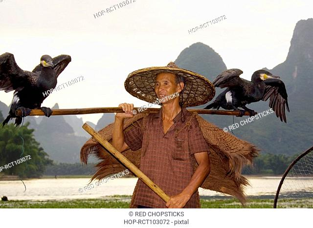 Senior man carrying two birds on his shoulders and smiling, Guilin Hills, XingPing, Yangshuo, Guangxi Province, China