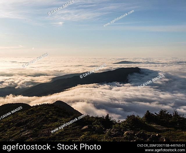 Bigelow Mountain rises out of sea of mist and fog at sunrise in Maine