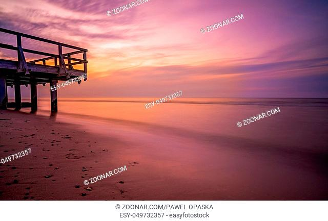 Panoramic picture of a sunset over wooden pier on the sea beach in Sarbinowo, Baltic Sea, Poland