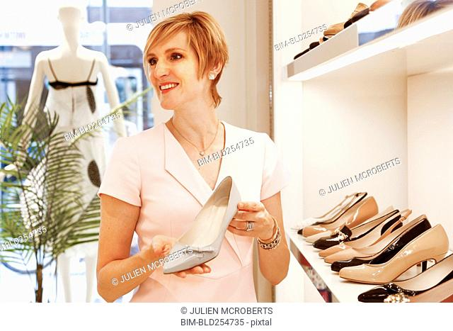 Smiling Caucasian woman holding shoe in store