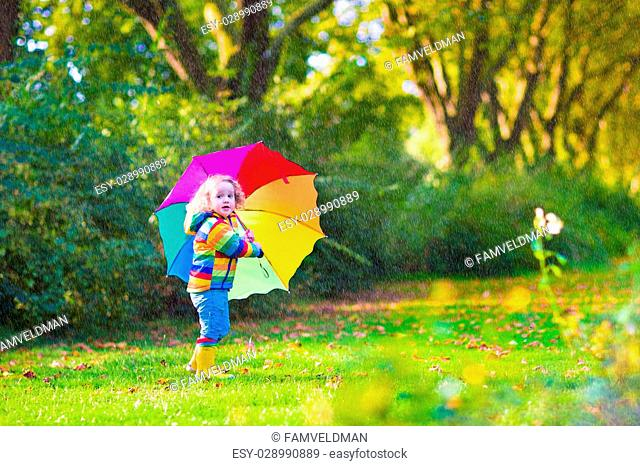 Funny cute curly toddler girl wearing yellow waterproof coat and boots holding colorful umbrella playing in the garden by rain and sun weather on a warm autumn...
