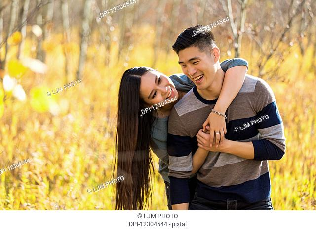 A young Asian couple enjoying quality time together outdoors in a park in autumn and embracing each other in the warmth of the sunlight during the early...