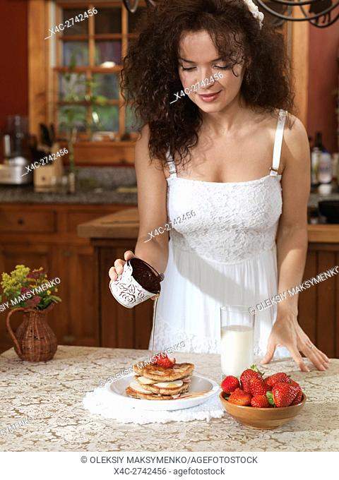 Young woman pouring maple syrup on pancakes with strawberries an apples in the kitchen