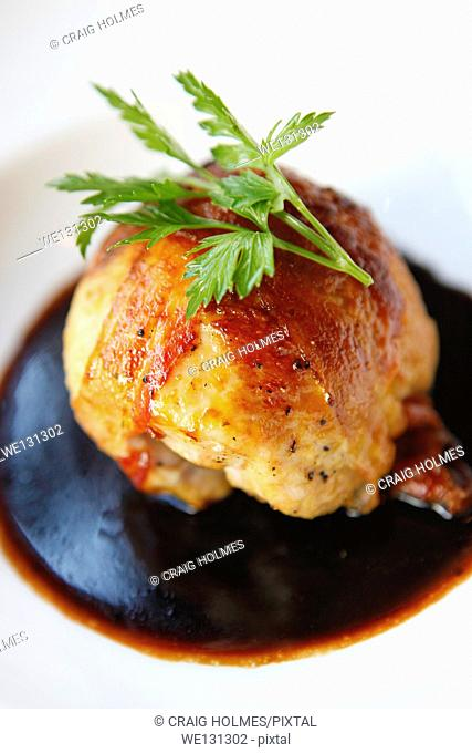Breast of Chicken, pancetta wrapped, with a sprig of flat leaf parsley