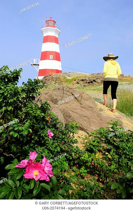 A woman walking up a slope to view the Brier island lighthouse in Nova Scotia, Canada