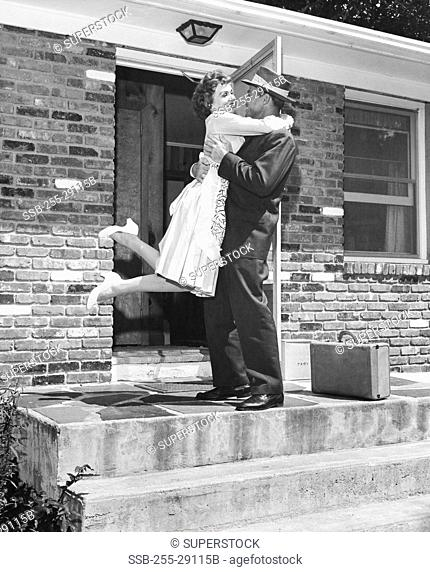 Mid adult couple embracing outside house
