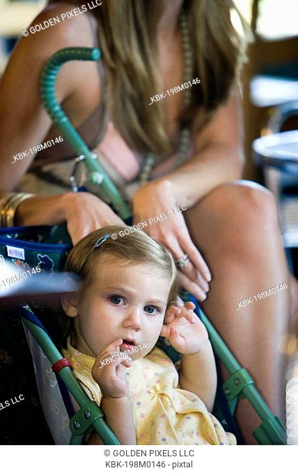 Baby girl sitting in stroller in cafi with mom in background