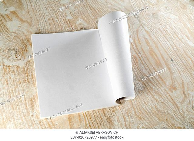 Photo of blank opened magazine or album on light wooden background with soft shadows. Template for design presentations and portfolios