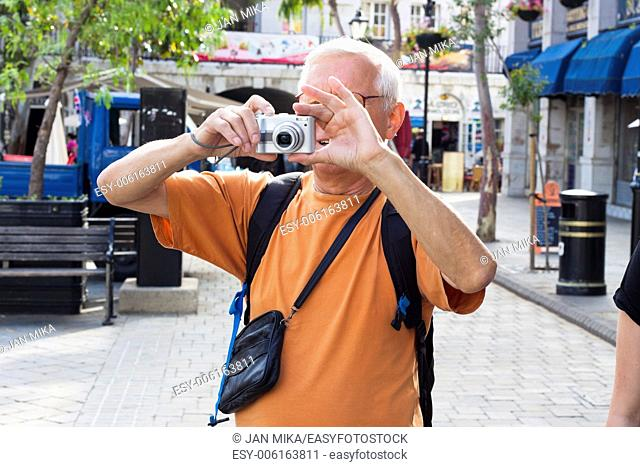 Senior man tourist taking photos using compact camera
