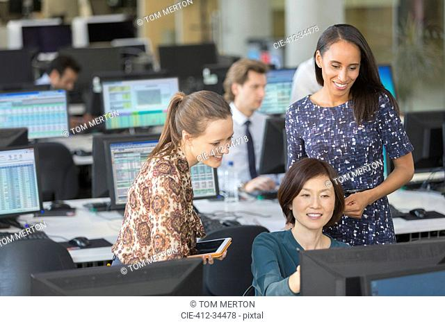 Businesswomen using computer in open plan office
