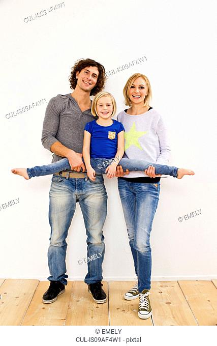Studio portrait of couple holding up daughter