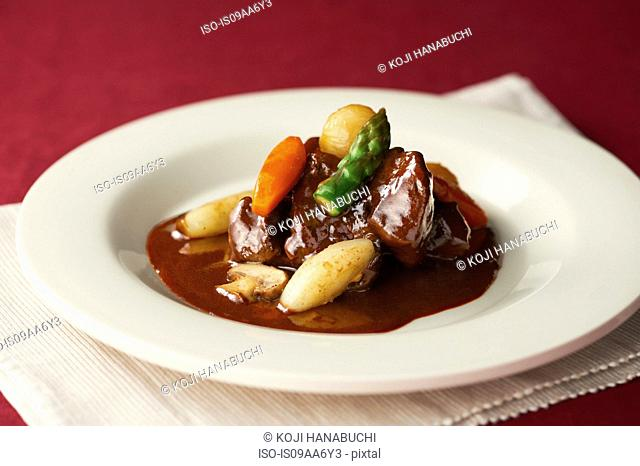 Still life of stew garnished with asparagus and carrot