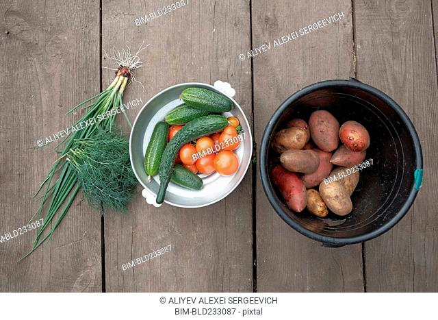 Fresh vegetables and potatoes on wooden table