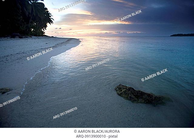 Small rock in warm crystal blue water at sunset in the tropics