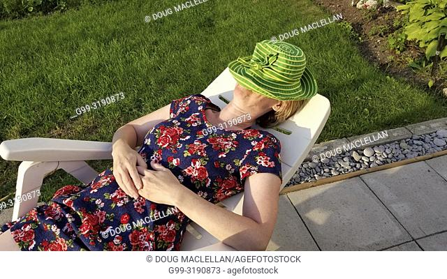 Woman in colourful dress and green hat napping on a plastic chair, Consecon, Canada