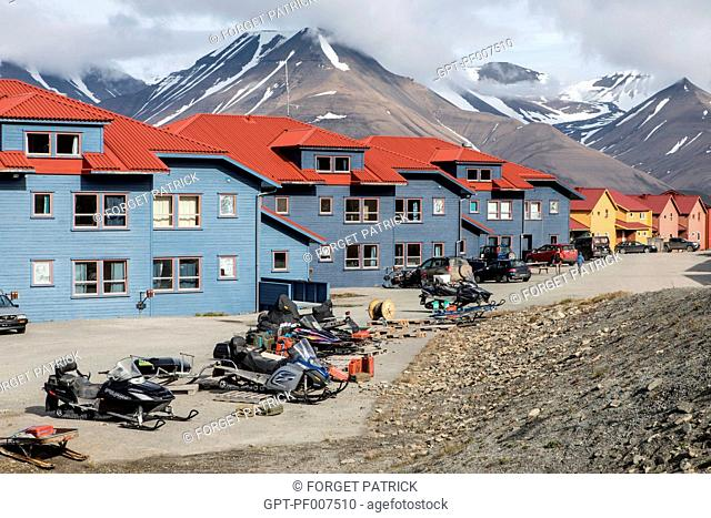 SNOWMOBILE IN FRONT OF THE COLORFUL WOODEN HOUSES, CITY OF LONGYEARBYEN, THE NORTHERNMOST CITY ON EARTH, SPITZBERG, SVALBARD, ARCTIC OCEAN, NORWAY