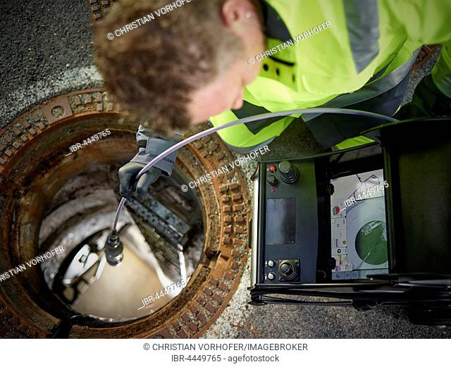 Sewer cleaning, inspection with video probe, worker looking at screen, Innsbruck, Tyrol, Austria
