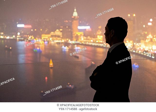The silhouette of a man looking out to the illuminated Pudong skyline from the Hyatt on the Bund Hotel