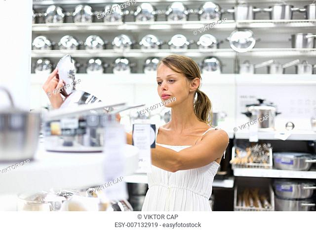 Pretty, young woman choosing a the right pot for her cooking in a modern home furnishings store (color toned image shallow DOF)