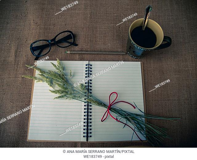 Vintage style. Organized desk with open notebook, a cup of coffee, dry grass, eye glasses, pencils and burlap background