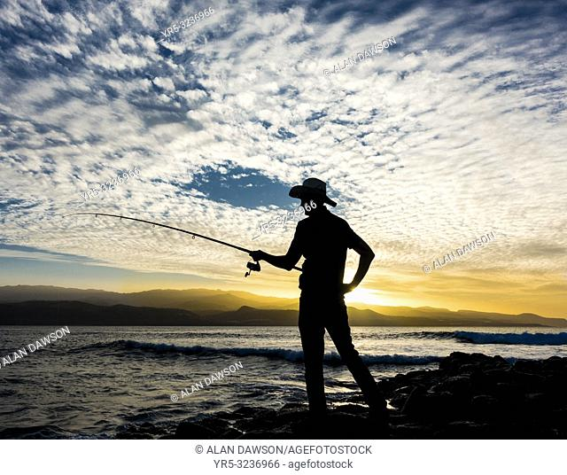 Las Palmas, Gran Canaria, Canary Islands, Spain. Man fishing on the north coast of Gran Canaria at sunset. Model released