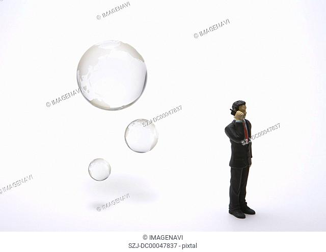 Glass globe and miniature businessman talking on mobile phone