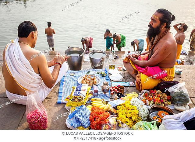 A Pandits (holy man and priest who performs ceremonies) preparing offerings and praying, on the ghats of Ganges river, in background pilgrims bathing, Varanasi