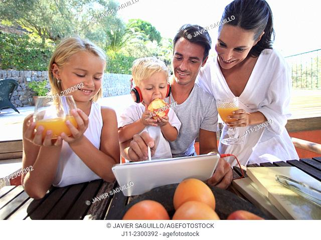 Family, looking at digital tablet