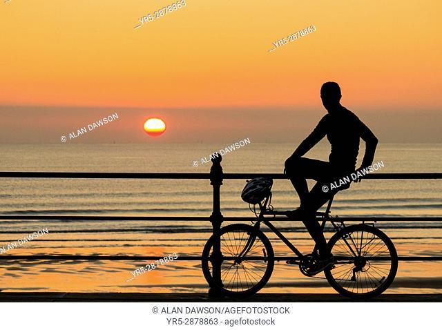 Seaton Carew, County Durham, north east England. United Kingdom. A mountain biker watches a stunning sunrise over the North sea