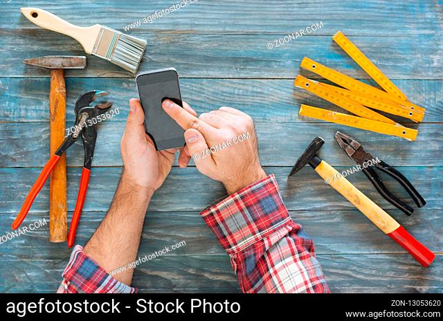 Man working on a DIY project with his phone, wood shavings and carpentry tools and construction all around, top view