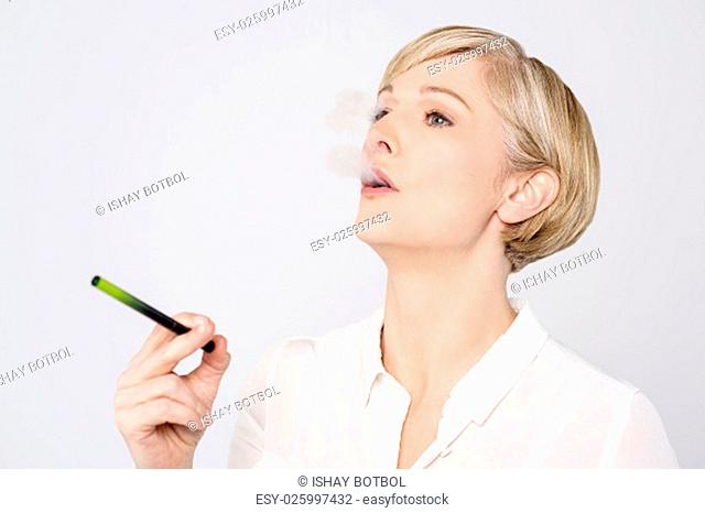 Woman using alternative cigar over grey