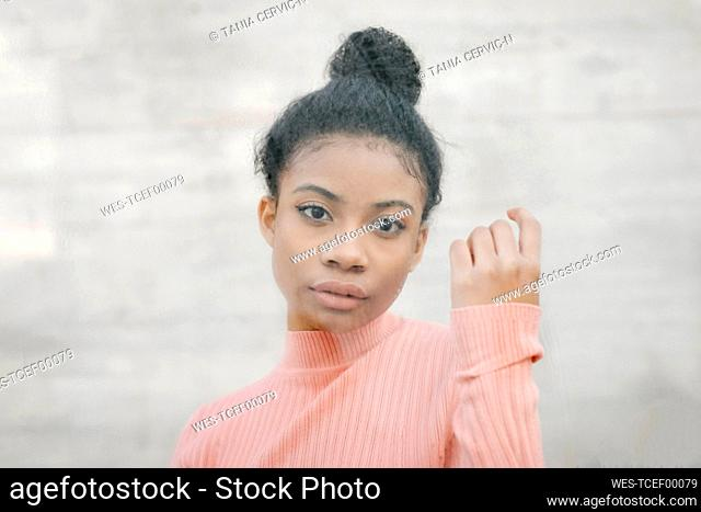 Portrait of a beautiful young woman behind glass pane