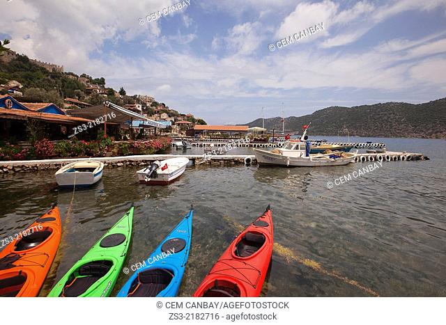 View to the Kalekoy the ancient city of Simena with colorful Kayaks in the foreground, Kalekoy, Antalya Region, Turkish Riviera, Turkey, Europe