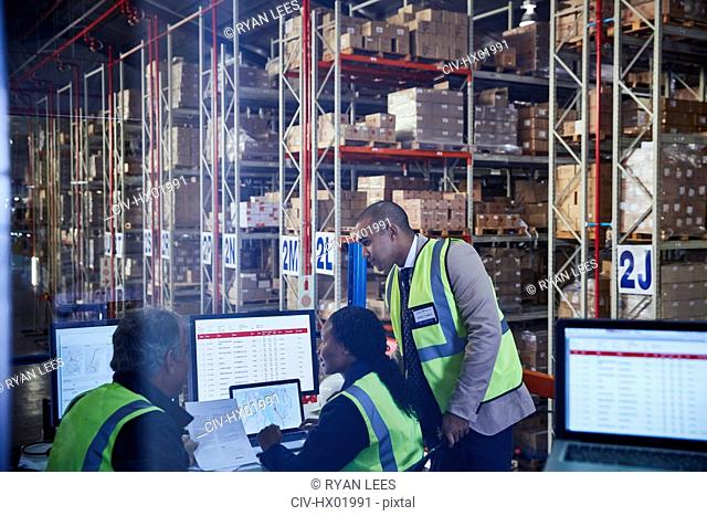 Managers meeting working at laptop and computers in distribution warehouse