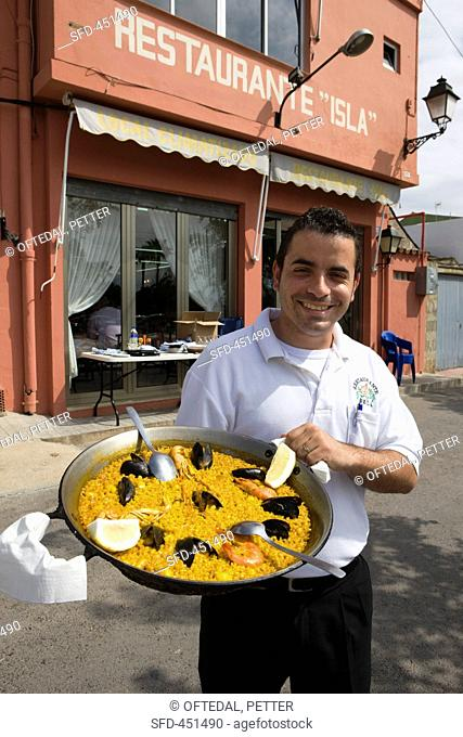 A waiter holding a paella in front of Restaurent Isla El Palmer, Valencia, Spain
