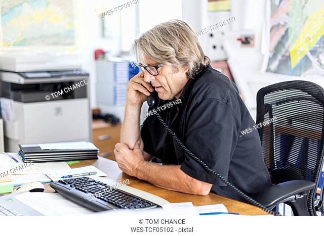 Mature man telephoning at desk in his office