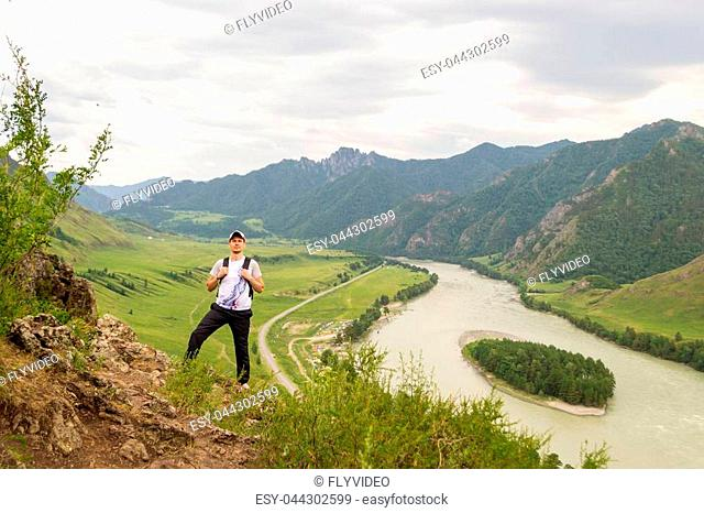 A young guy in a cap with a backpack and black sports pants is standing on the edge of a cliff in the mountains of the Altai