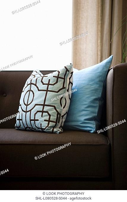 Detail blue throw pillows on chocolate brown sofa