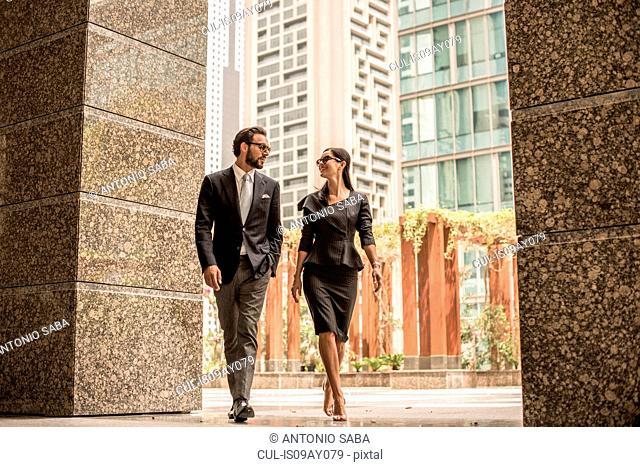 Businessman and woman walking and talking outside office, Dubai, United Arab Emirates