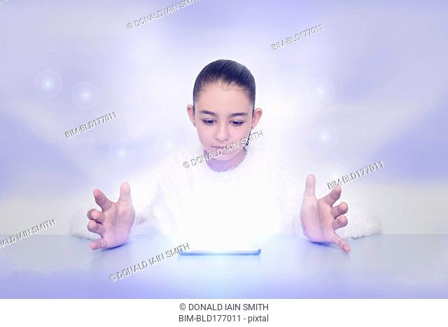 Mixed race girl with glowing digital tablet