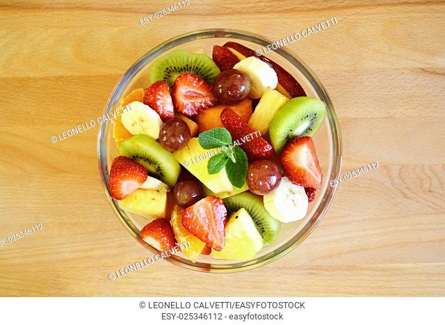 Fruit salad in a glass bowl viewed from top. On a wood surface