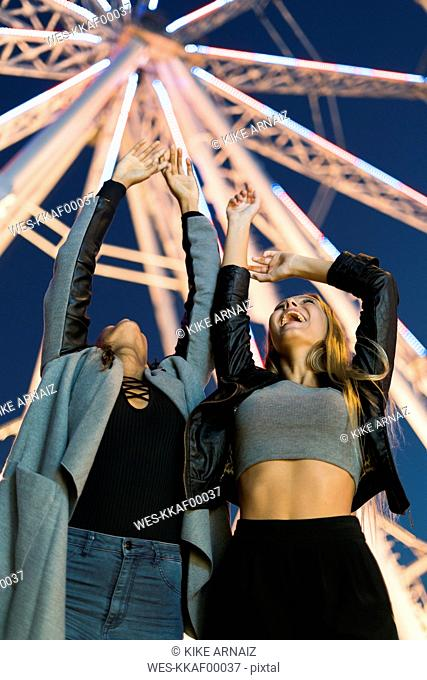 Two enthusiastic young women on a funfair at night