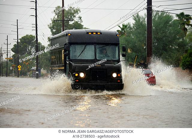 An United Parcel Service delivery truck drives through flooded streets during a monsoon storm, Sonoran Desert, Tucson, Arizona, USA