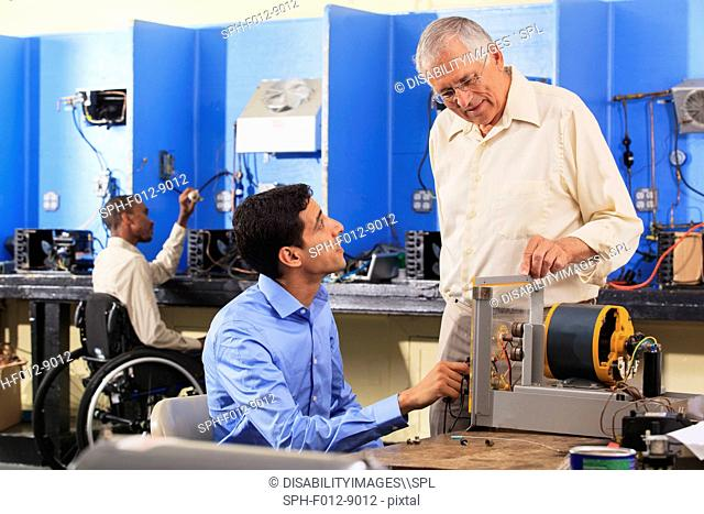 Student setting up generator experiment with professor while student in wheelchair examines HVAC system