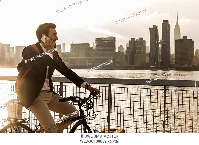 USA, New York City, businessman on bicycle talking on cell phone